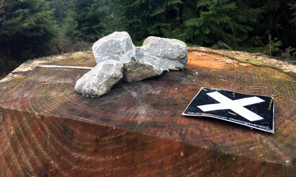 Baumstumpf mit Steinen und Wegweiser
