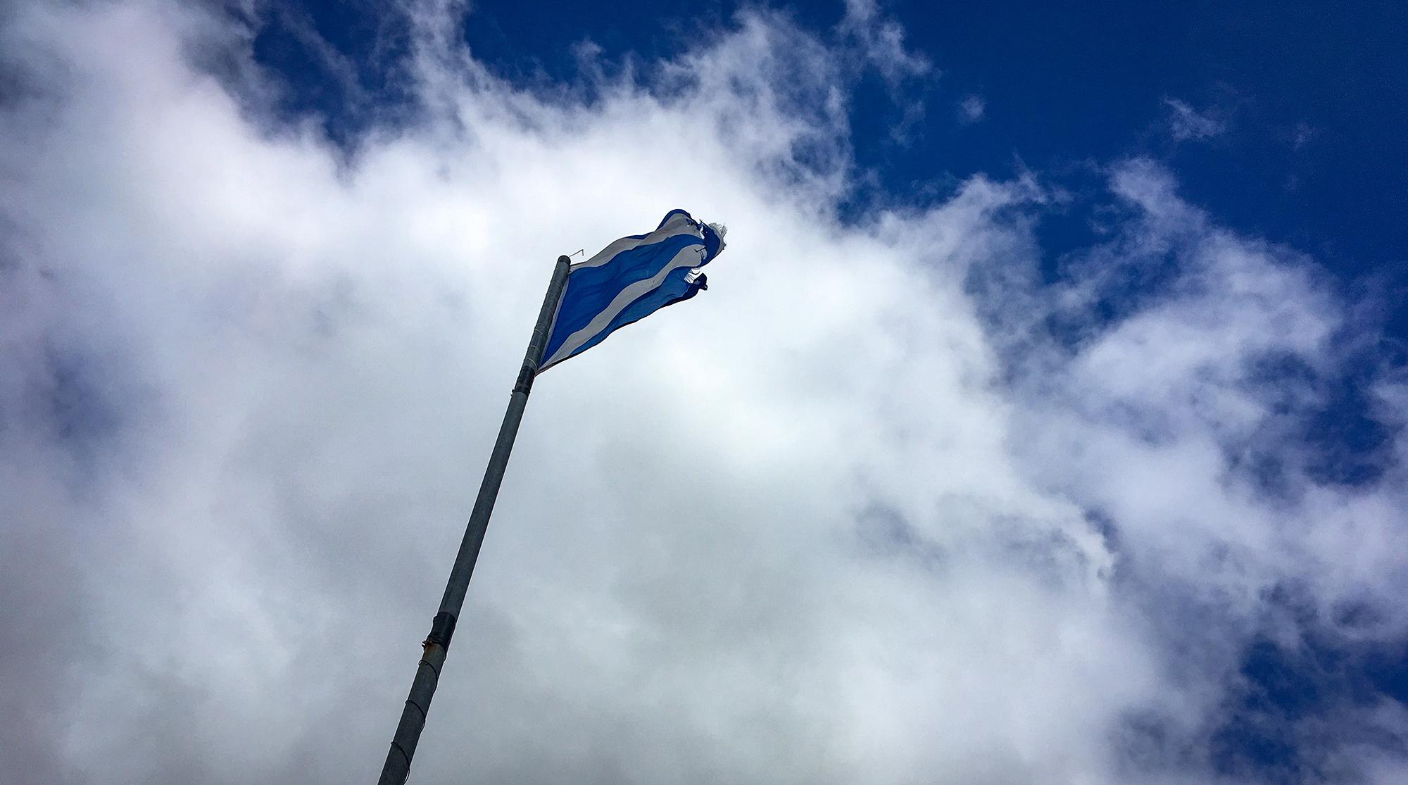 Schottische Flagge weht vor weißen QWolken und blauem Himmel