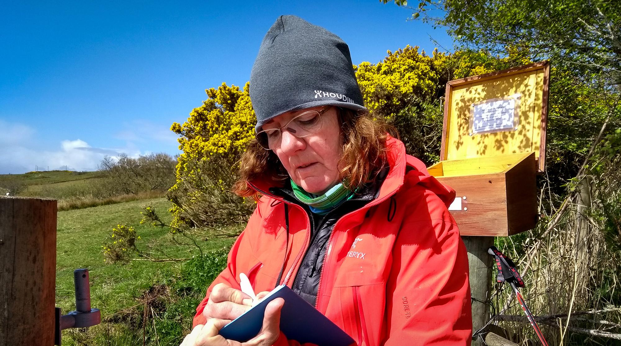 Frau sitzt vor einem Holzkasten und schreibt in das Johno'Gtoats Trailbuch