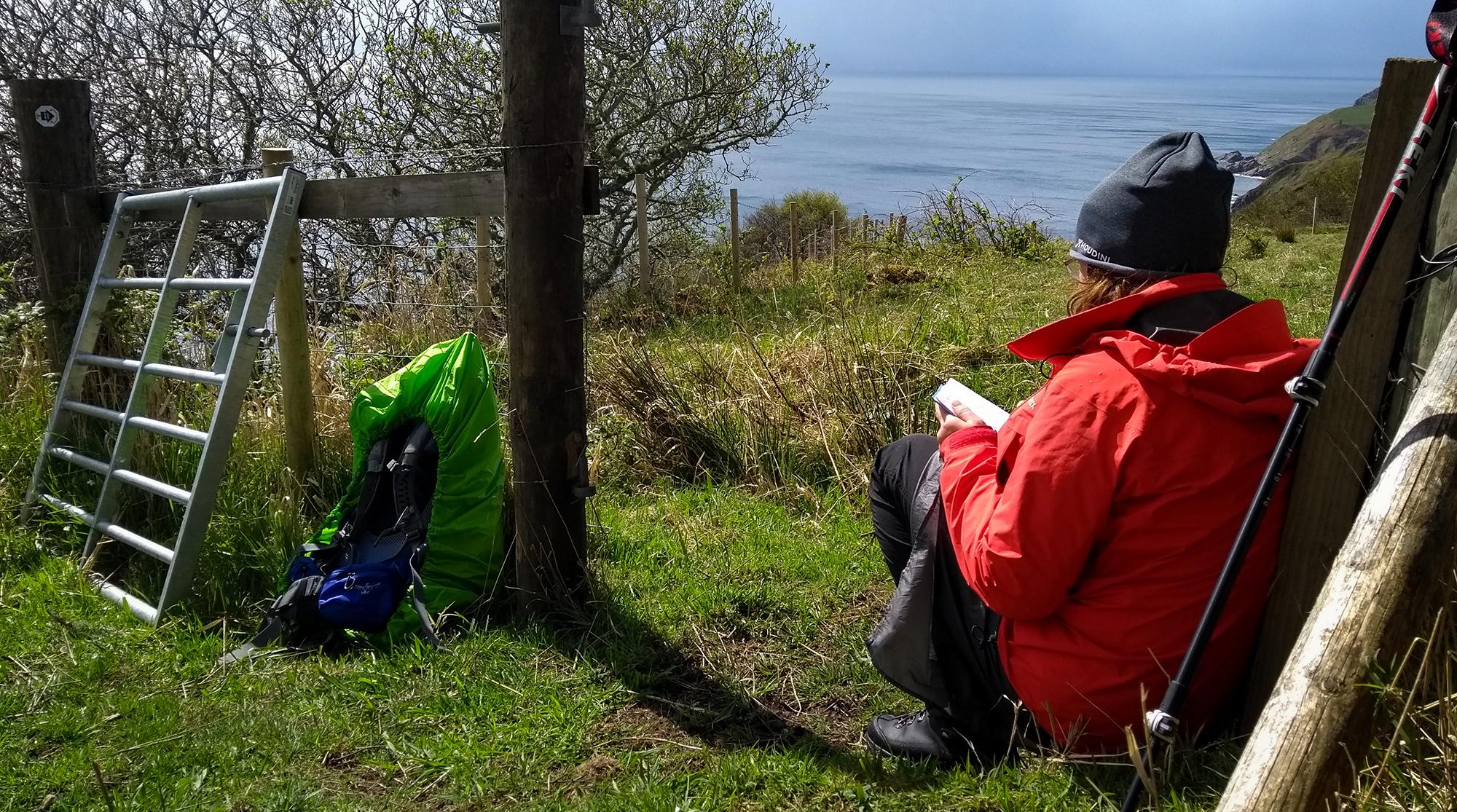 Frau sitzt an einem Zaun an einer Klippe und schreibt in ein Trailbuch