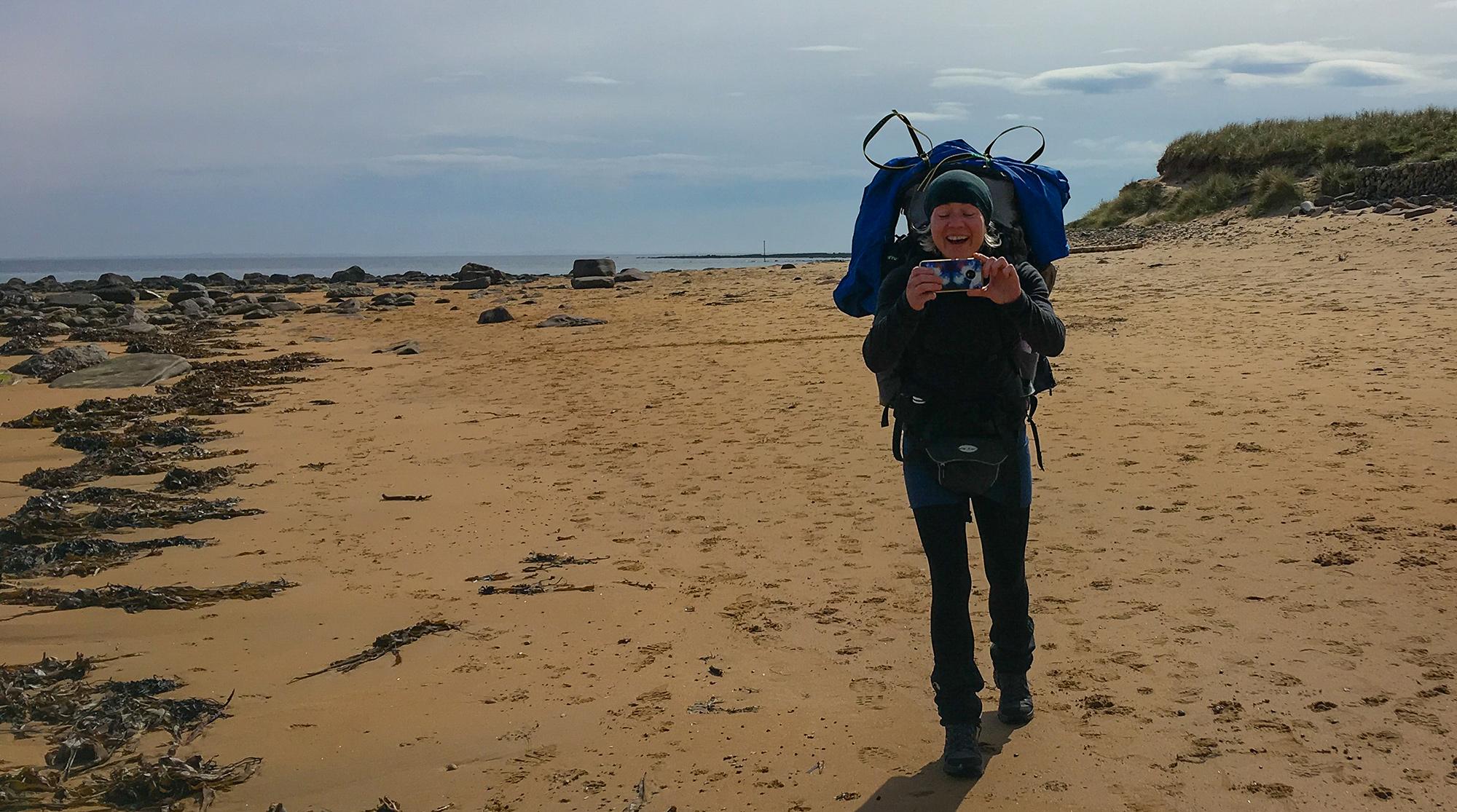 Frau mit Rucksack am Strand macht Foto