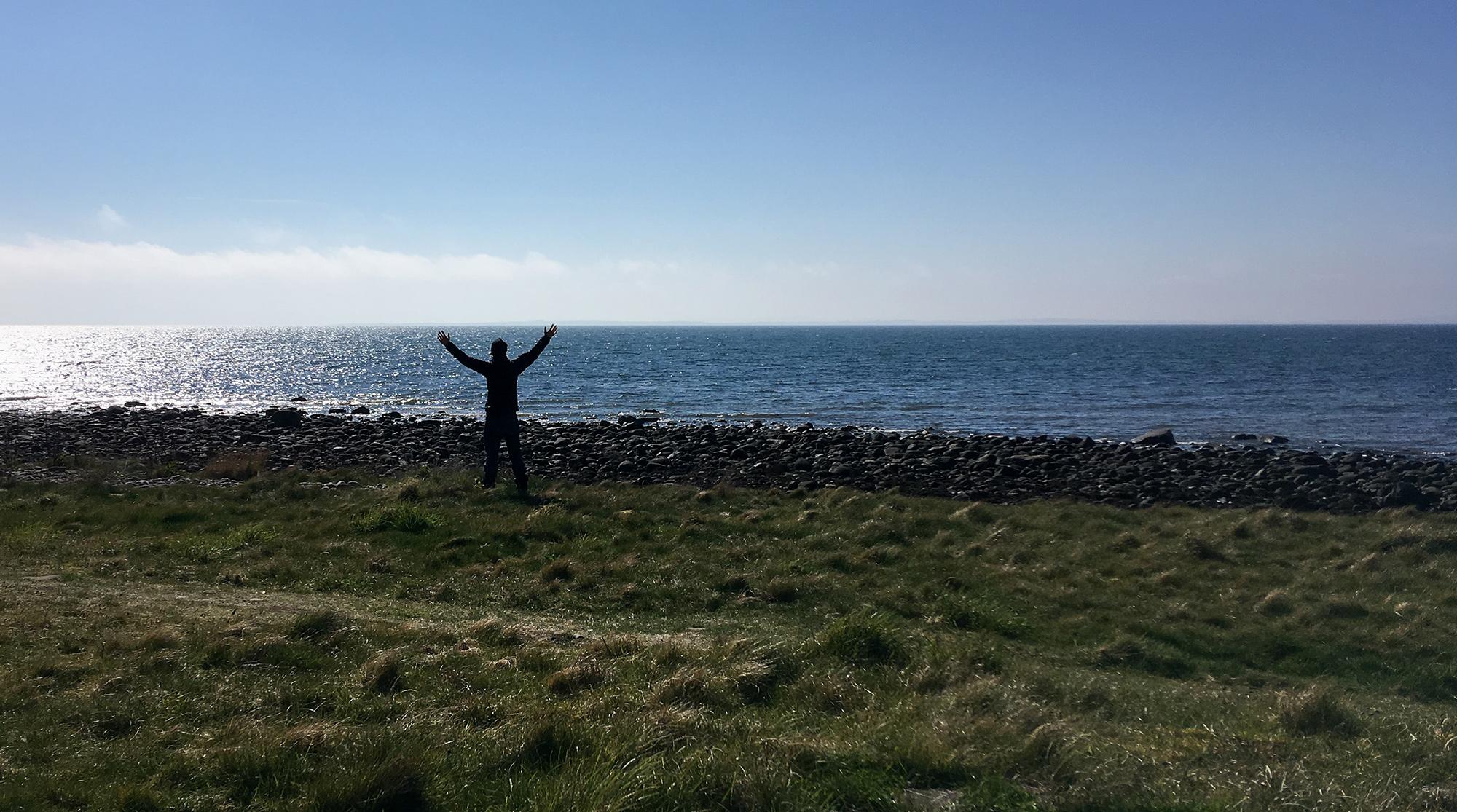 Frau mit ausgebreiteten Armen mit Meer beiGolspie im Hintergrund