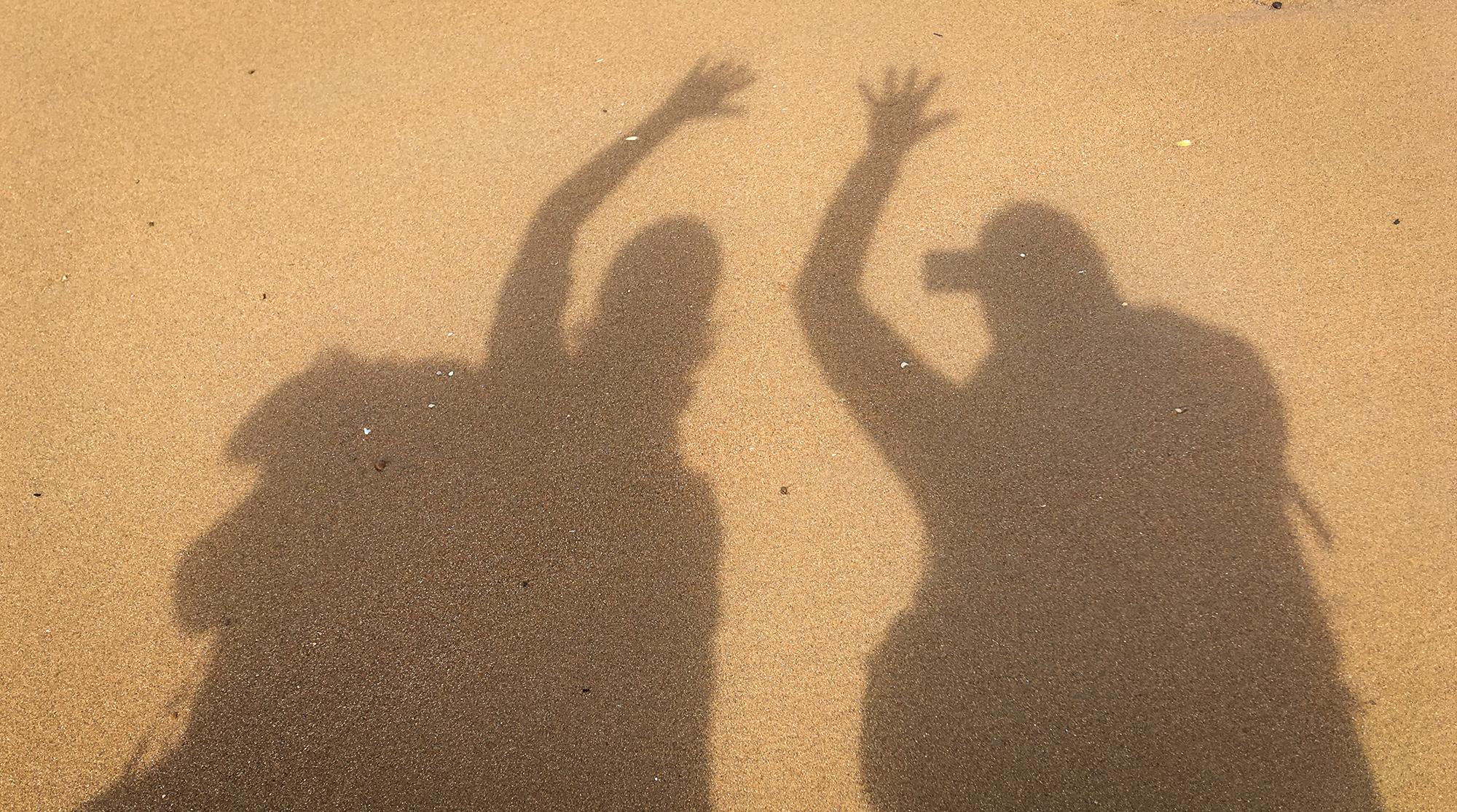 Schattenspiel mit zwei Frauen auf Sand