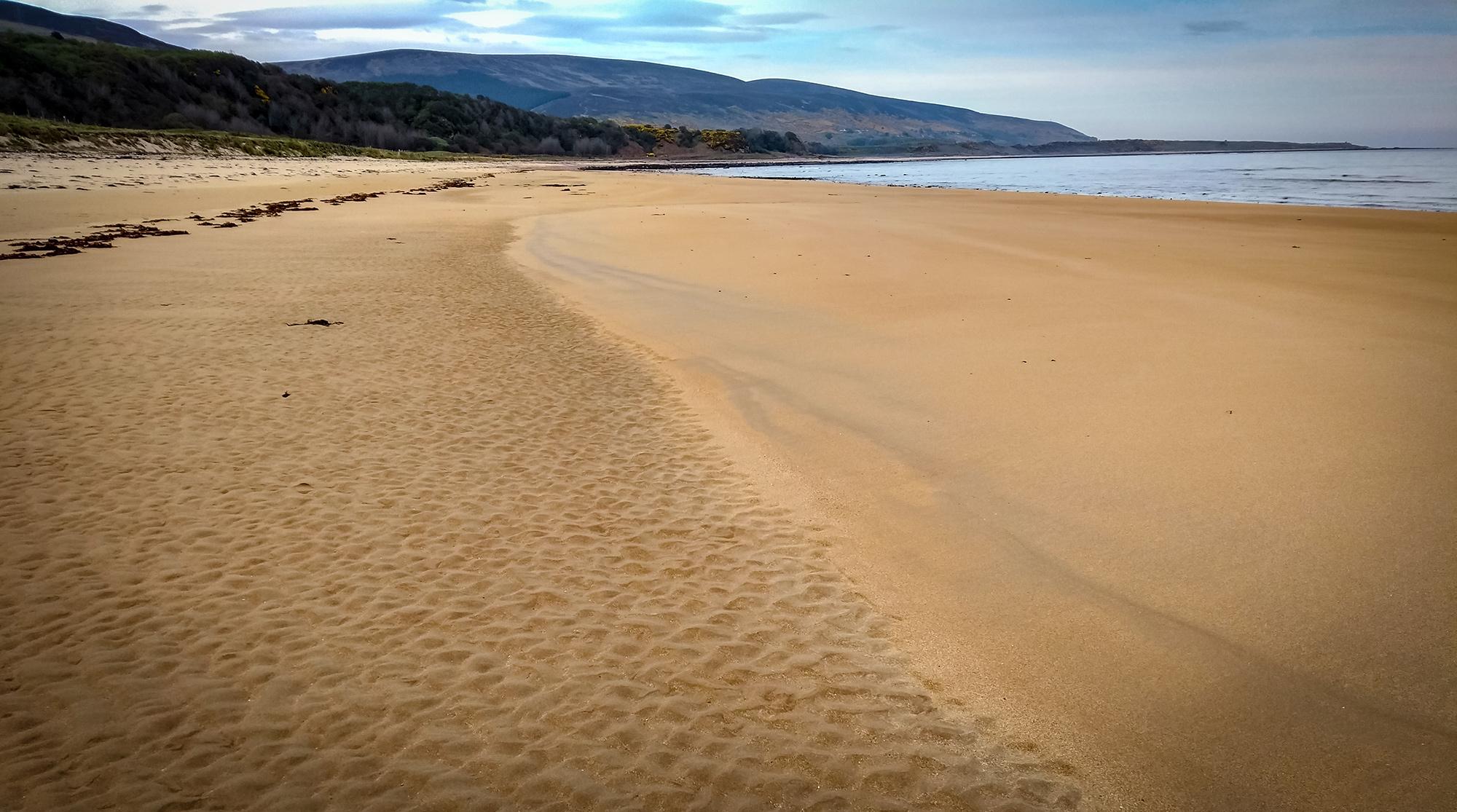 Brora Beach Breiter Sandsttand mit Meer und Hügeln