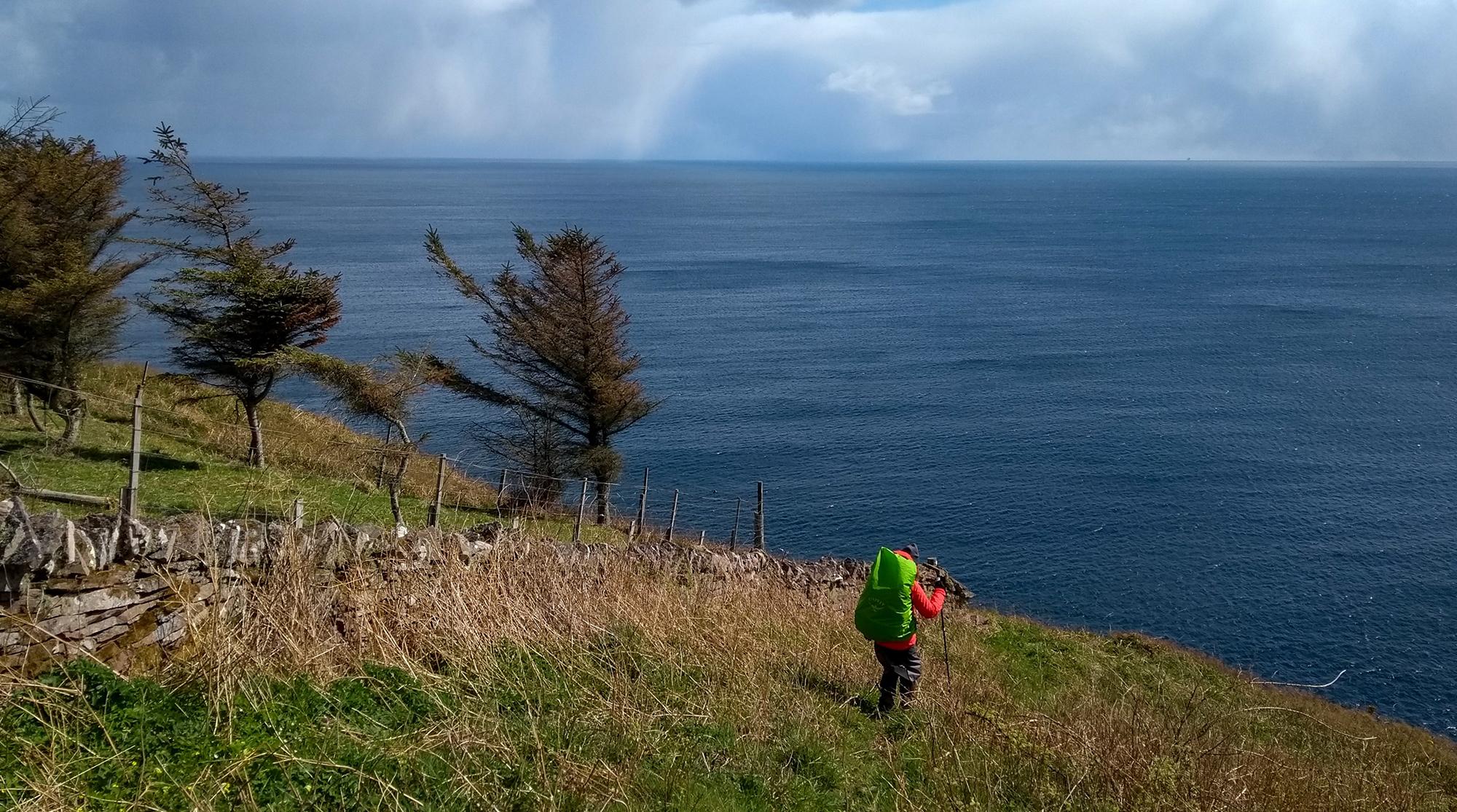 Frau mit Rucksack geht auf Gras an einr Steinmauer in Richtung Abgrund