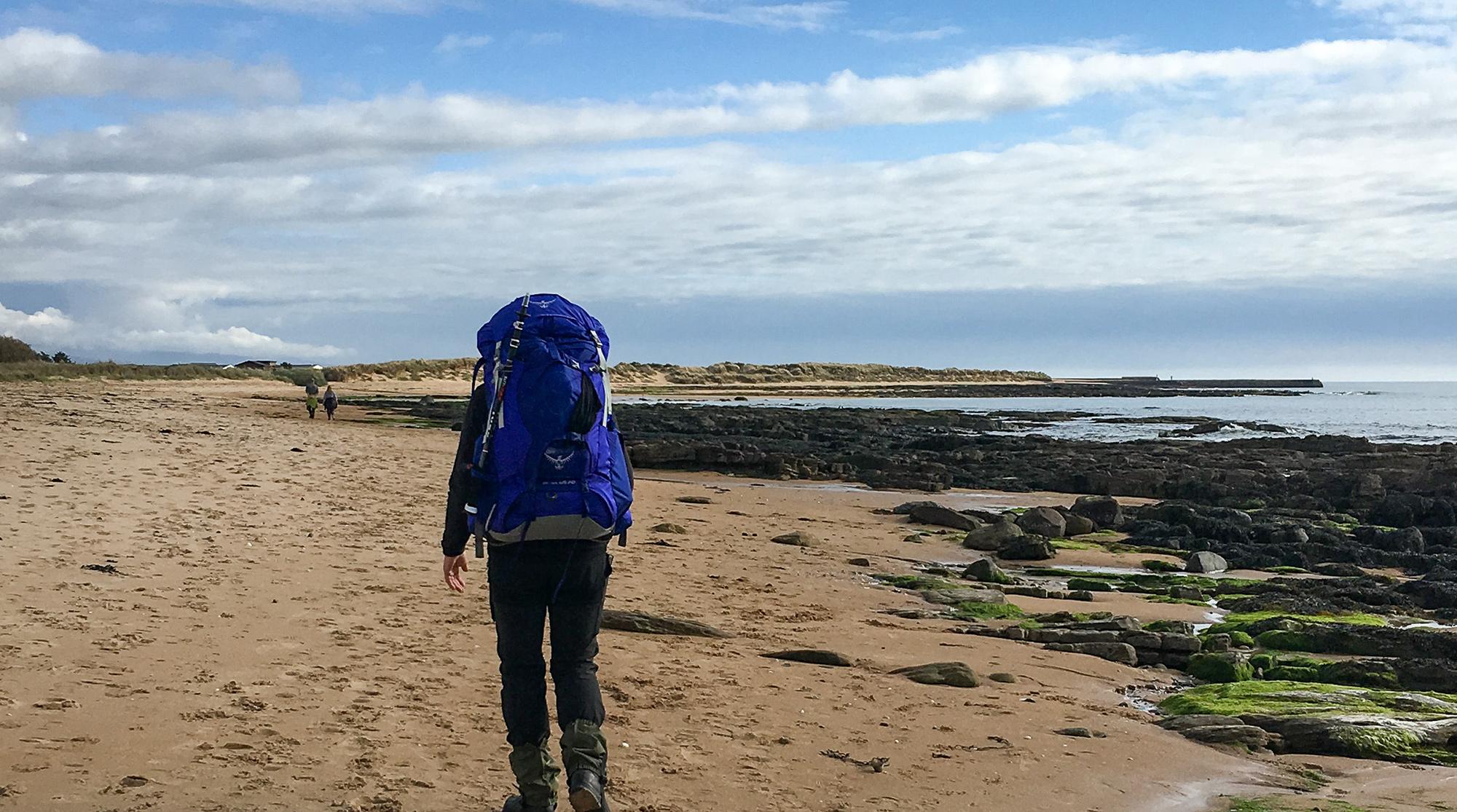 Frau mit Rucksack am strand wandernd