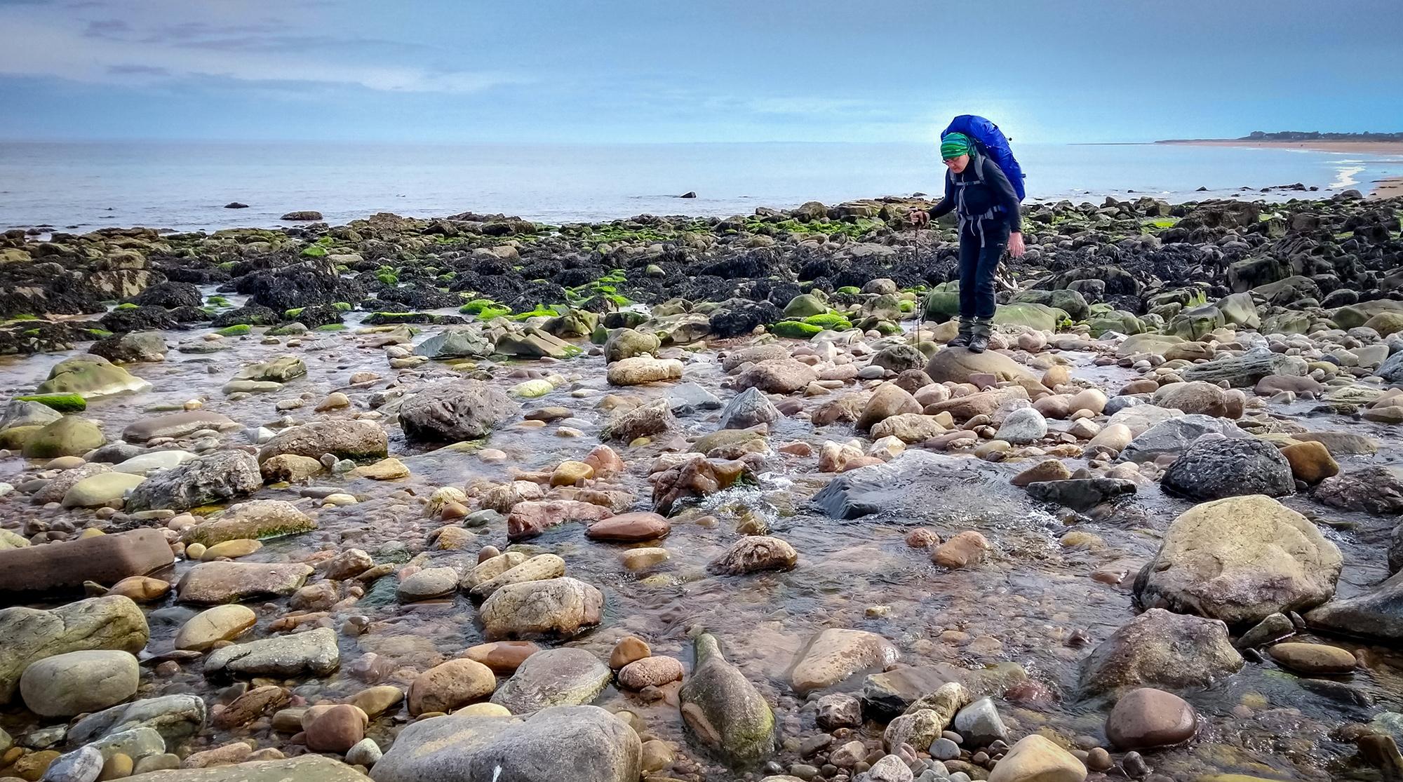 Frau mit Rucksack balanciert über Steine in einem Fluss