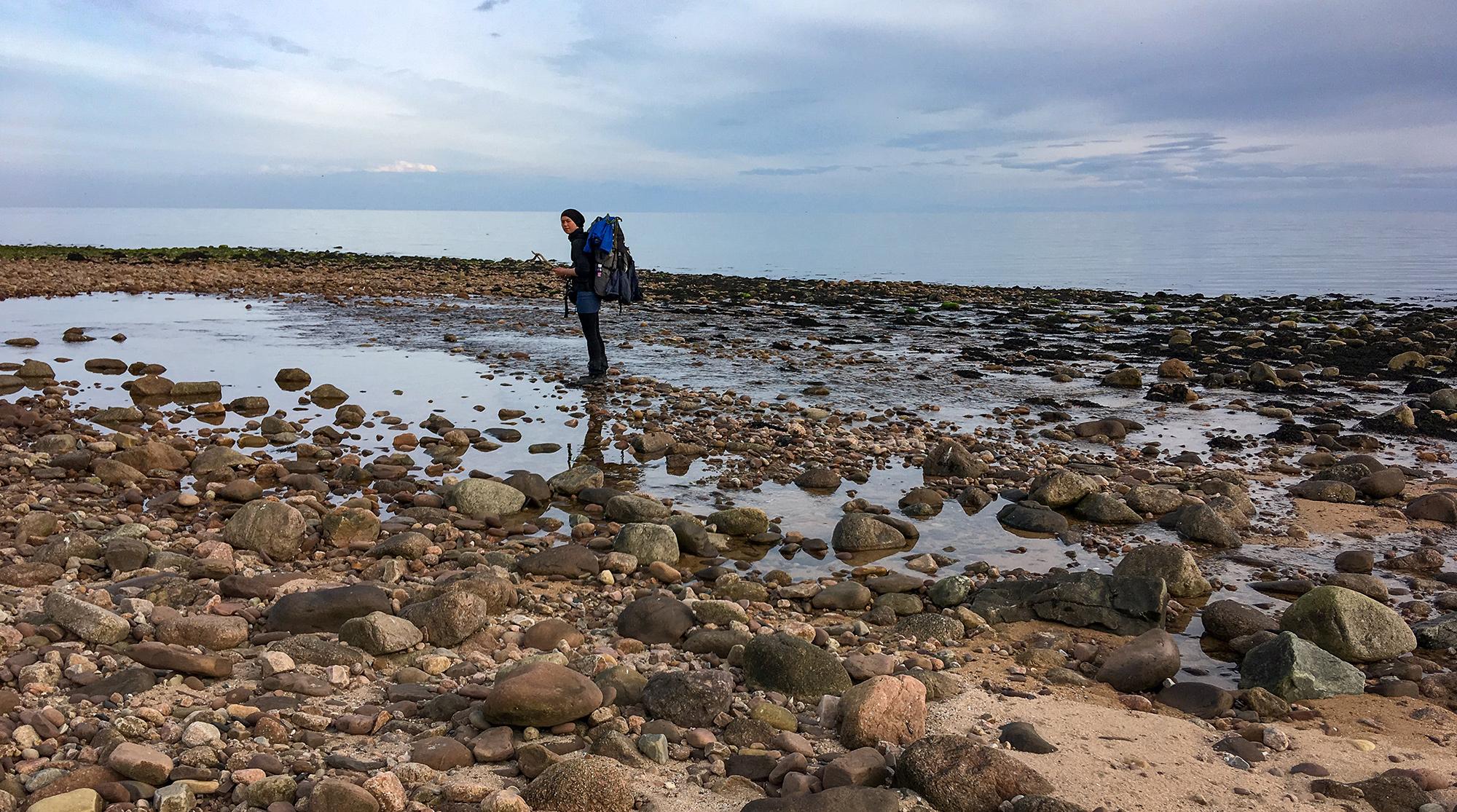 Frau mit Rucksack überquert Flusssbett mit Steinen am Meer