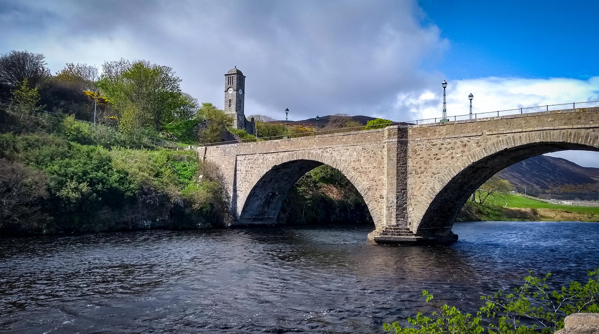 Steinbrücke über en Fluss Helmsdale mit Kirchturm im Hintergrund