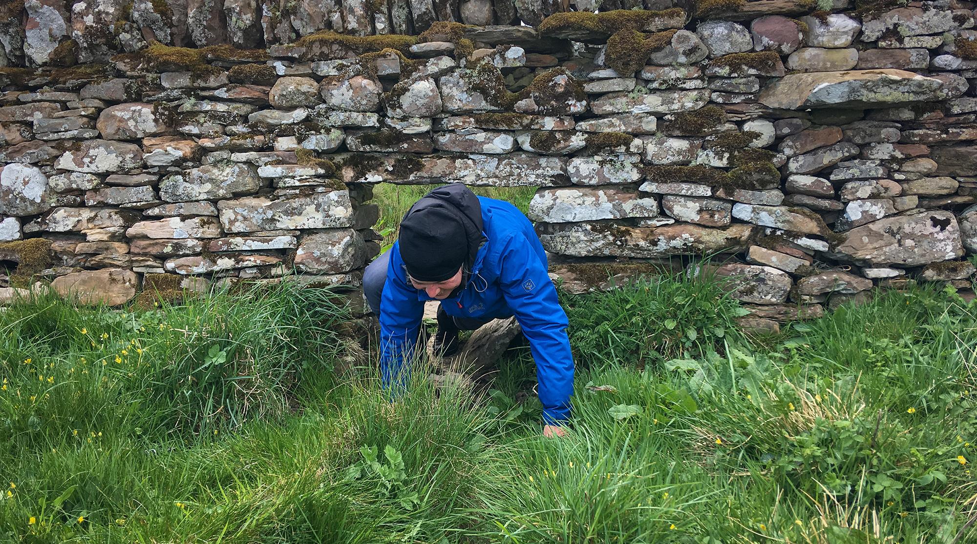 Frau krabblelt durch ein Loch in einer Steinmauer