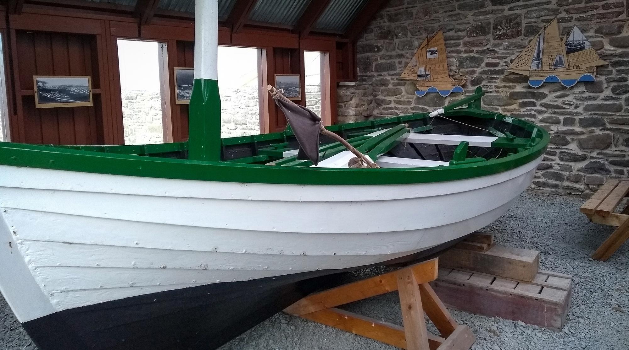 weißes Holzboot in einer Scheune mit Glasfenstern und Mauer in Dunbeath