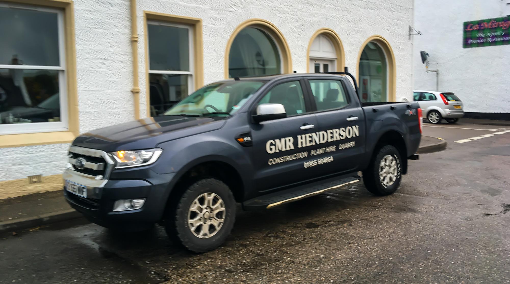 Pickup mit Aufschrift GMR Henderson vor einem Haus