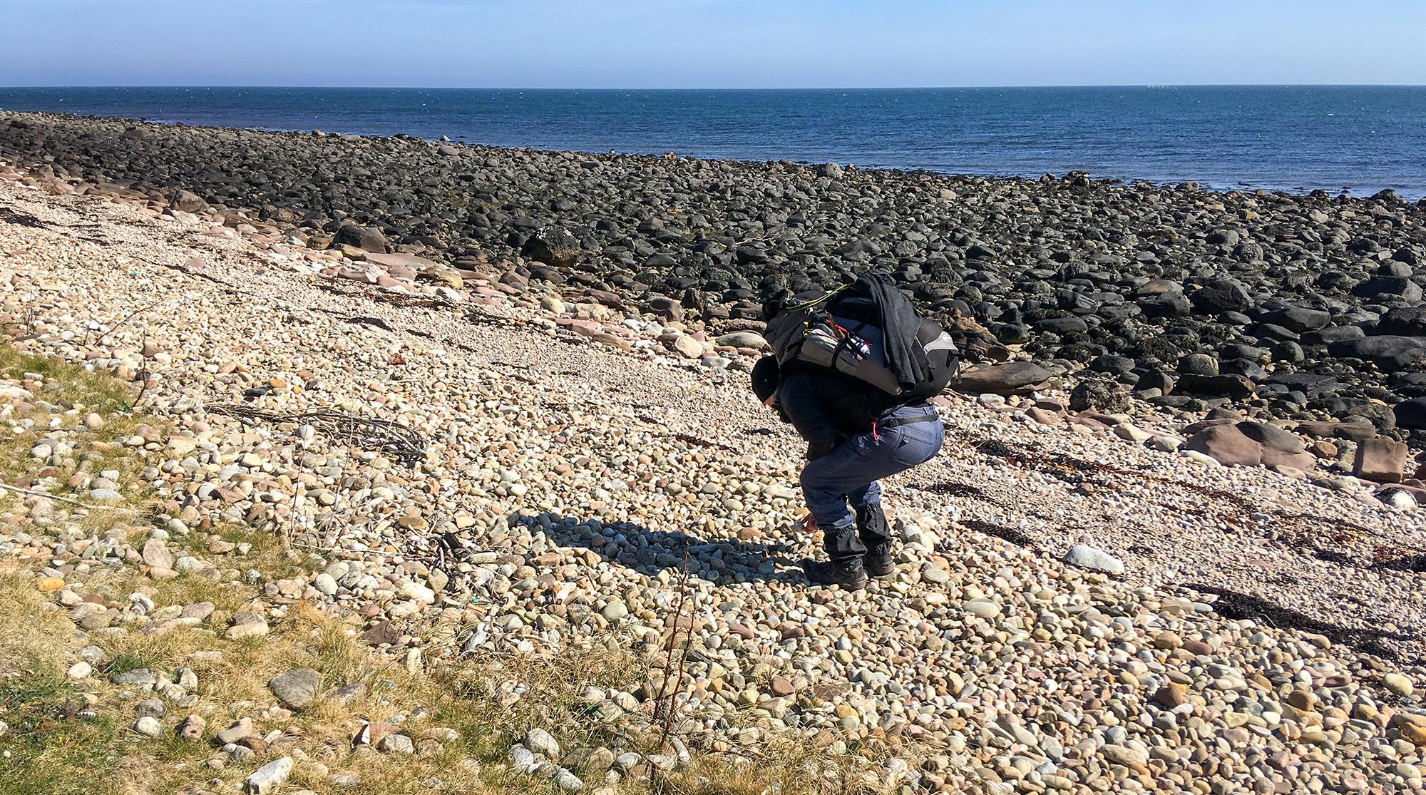 Frau mit Rucksack sammelt Steine am Strand