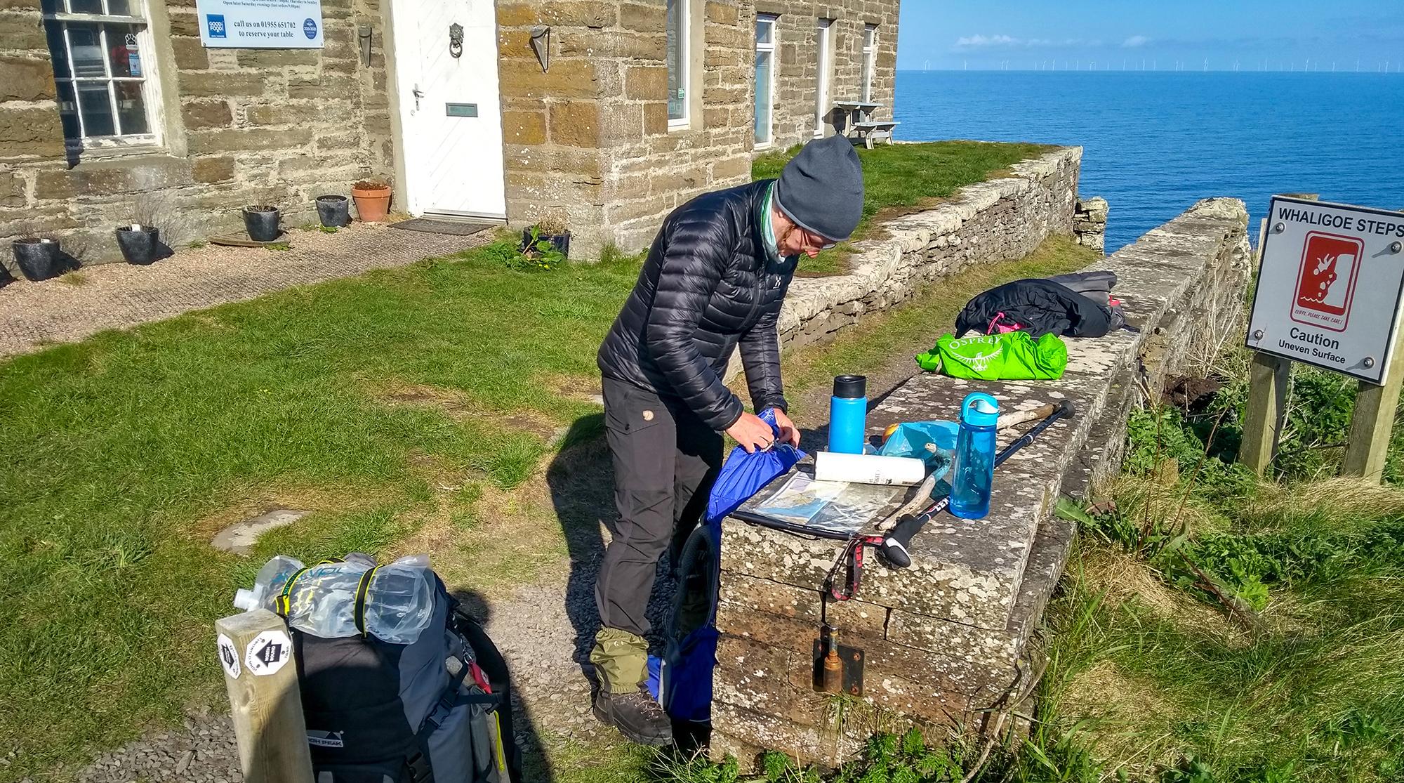 Frau packt Rucksack an MAuer an den Whaligoe Steps