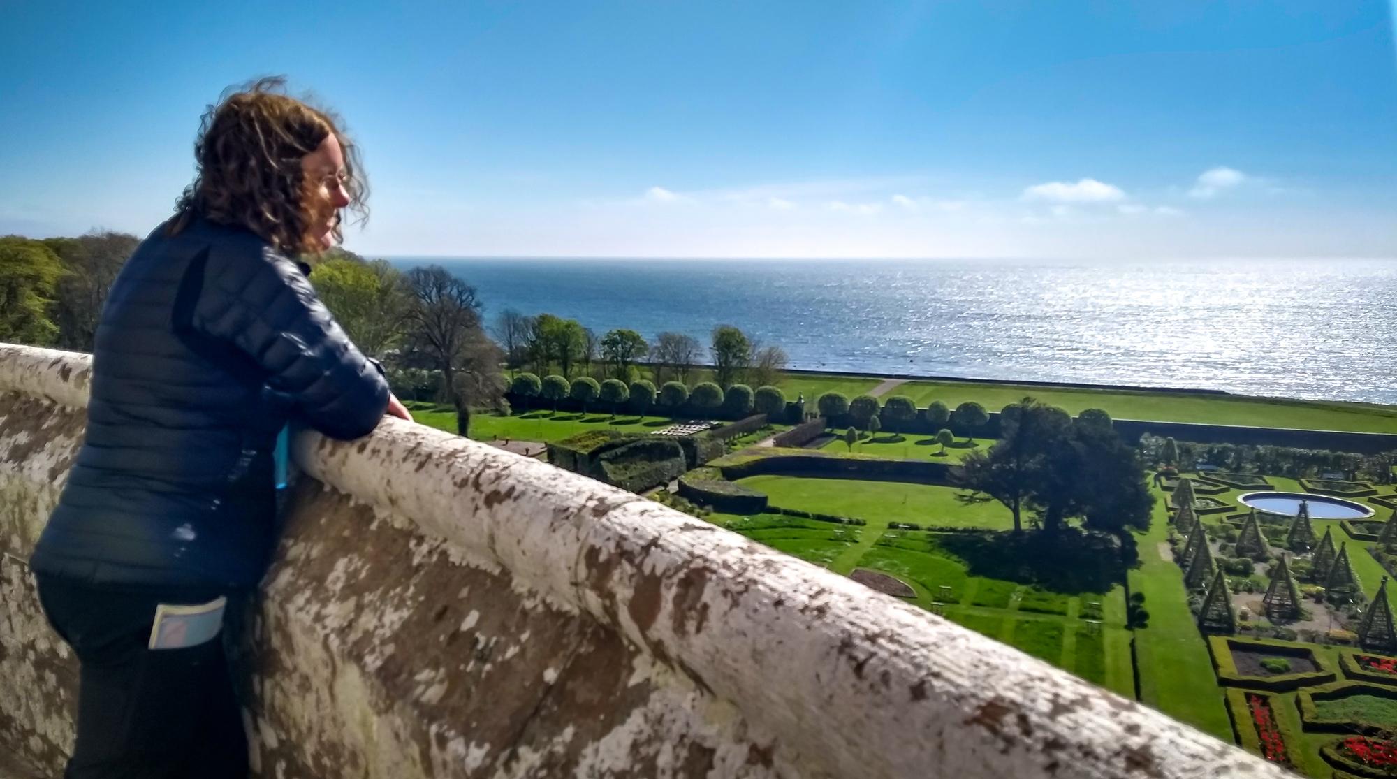 Frau blickt über den Garten von Dunrobin Castle auf das Meer