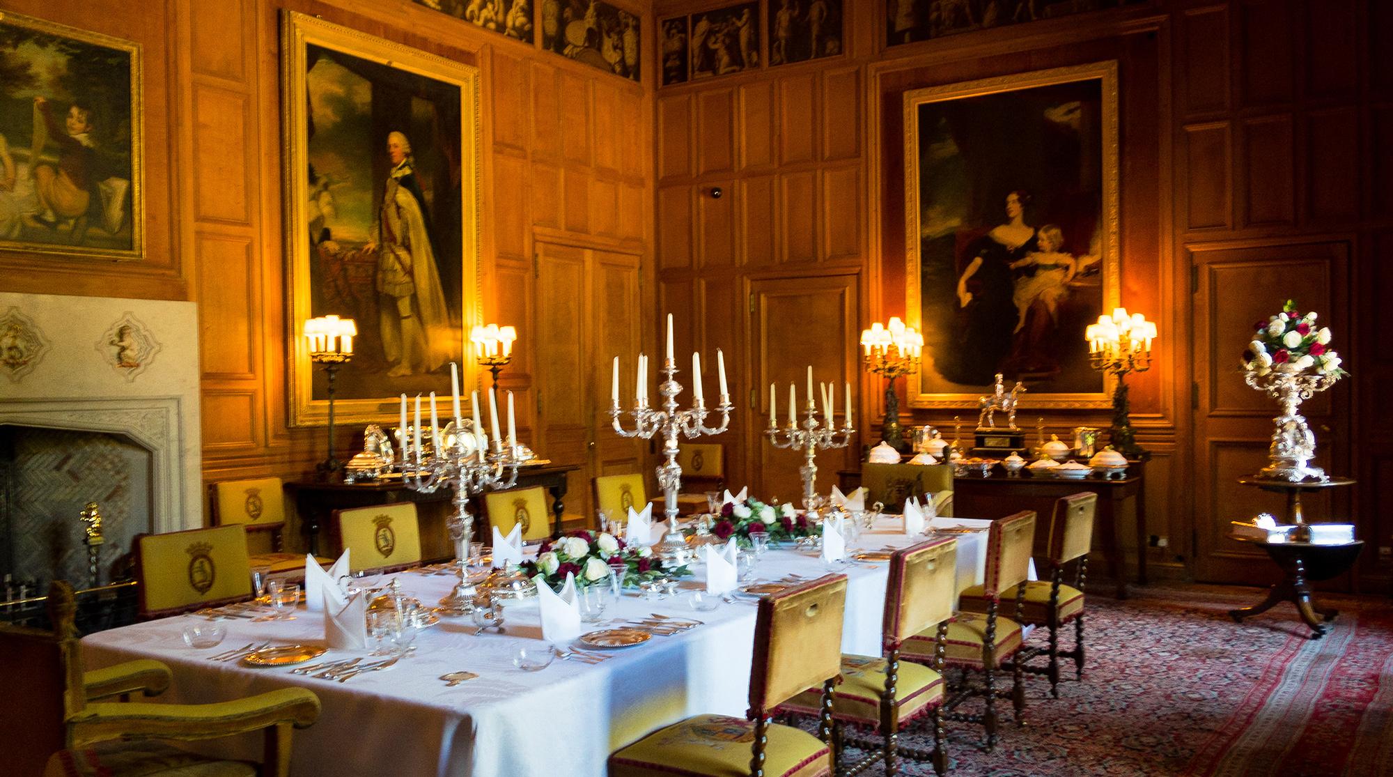 Soeisezimmer mit Kandelabern, und gedecktem Tisch in holzgetäfeltem Raum mit Ahnenbildern im Dunrobin Castle