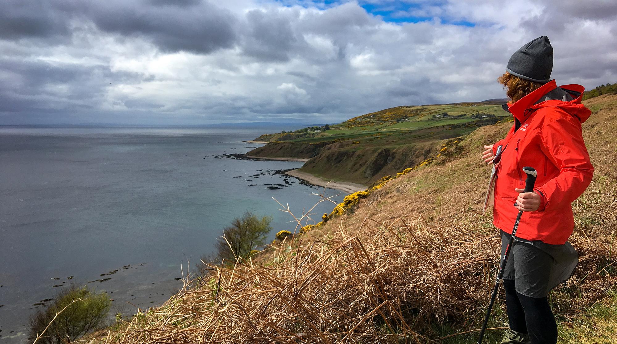 Frau auf einer Klippe am Meer in Schottland