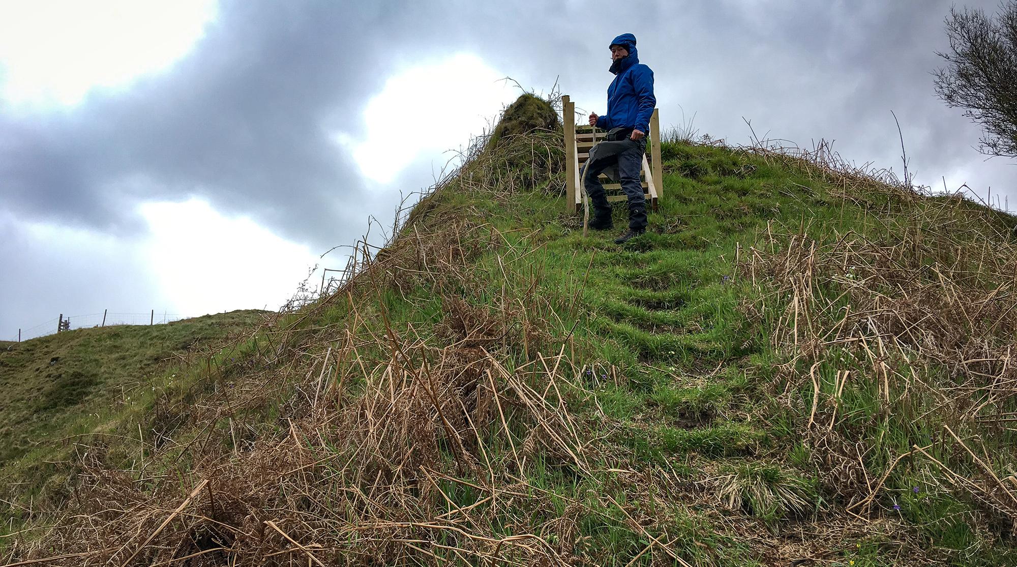 Frau steh vor einer Holztreppe an einem steilen Abstieg