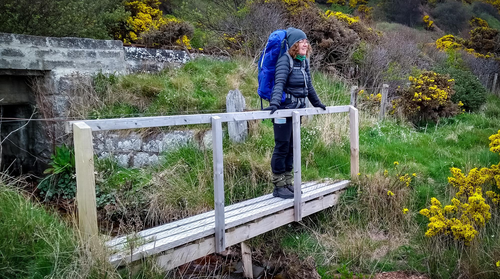 Frau auf einer Holzbrücke über einer Flussmündung