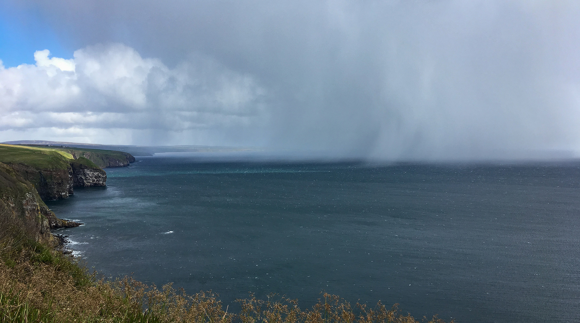 Regenschauer und dunkle Wolken über dem Meer mit Küstenpanorama