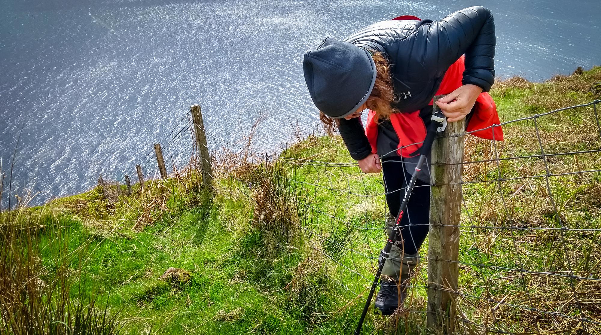 Frau klettert über einen Zaun auf einer steil abfallenden Klippe