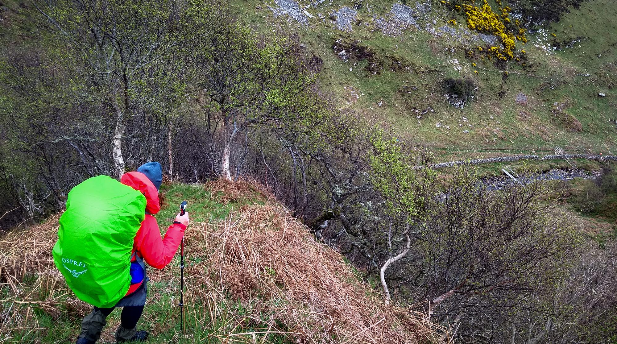 Frau geht einen steilen Abstieg am Ousdalehinunter