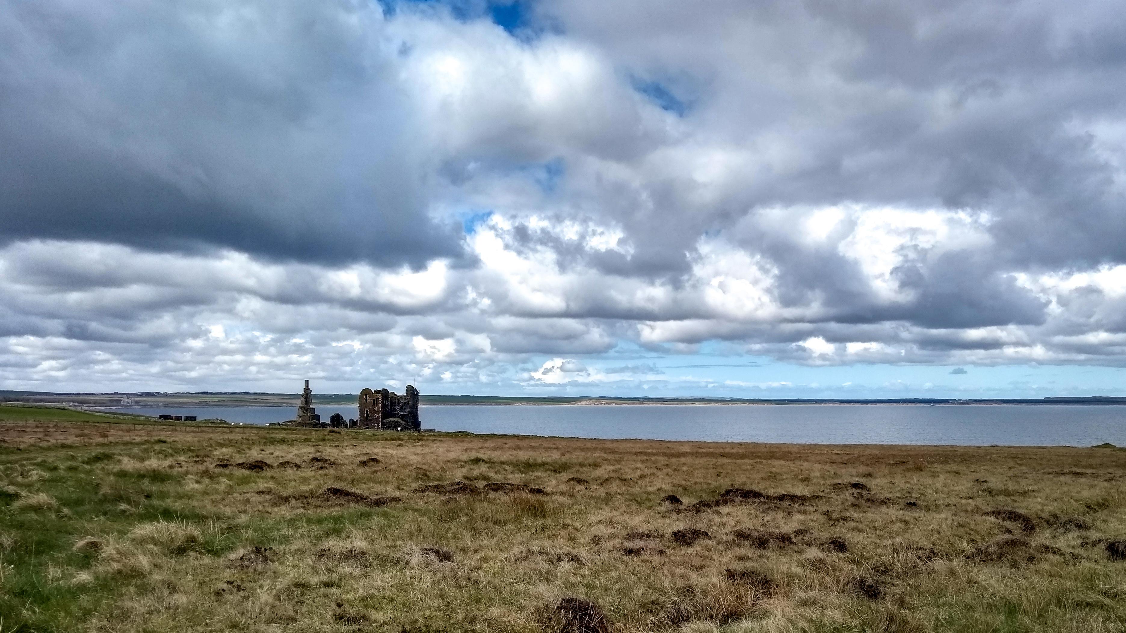 Blick auf eine Burgruine und eine weite Bucht
