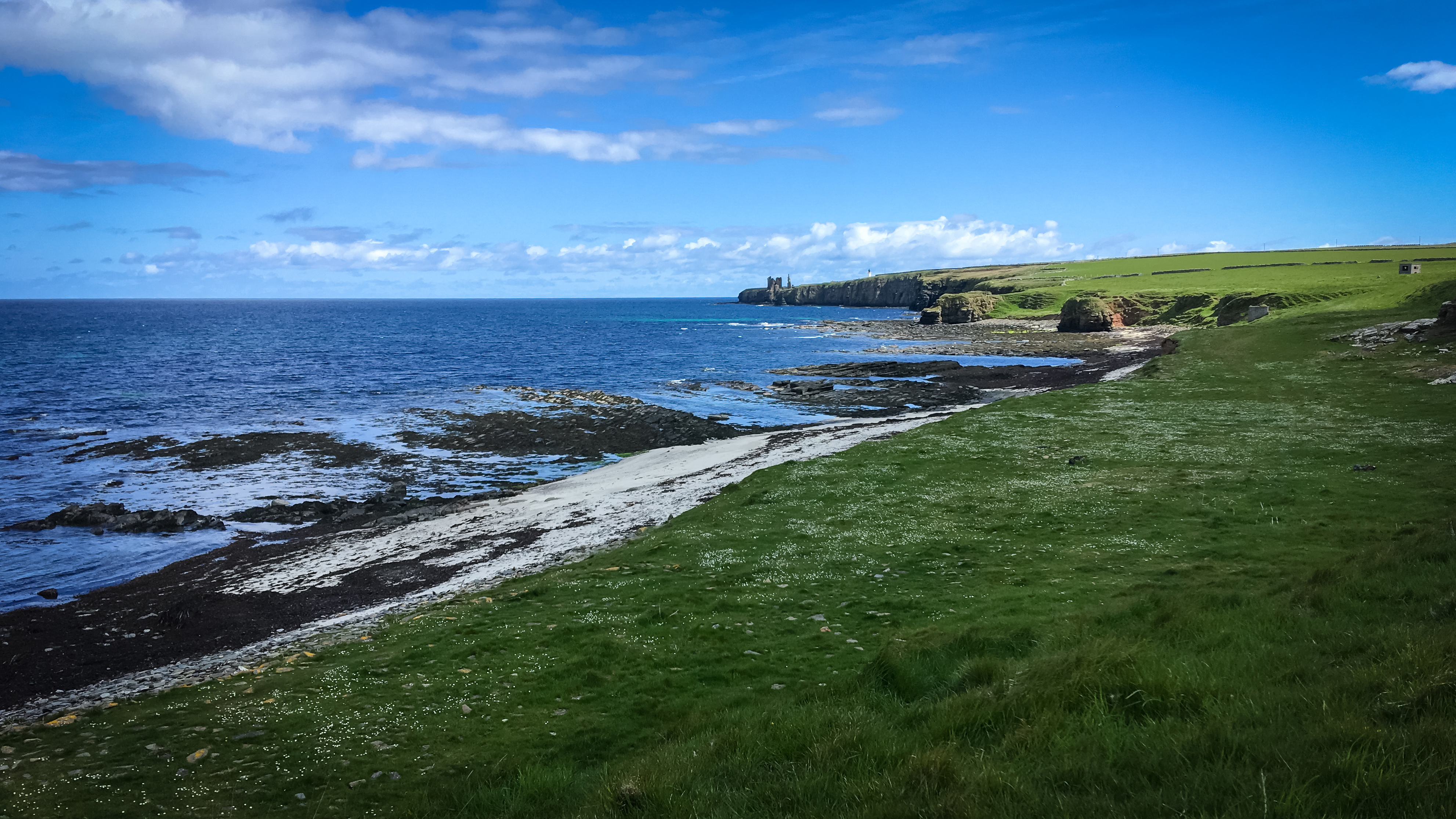 Klippenlandschaft am Meer mit Burgruine Sinclair und Leuchtturm