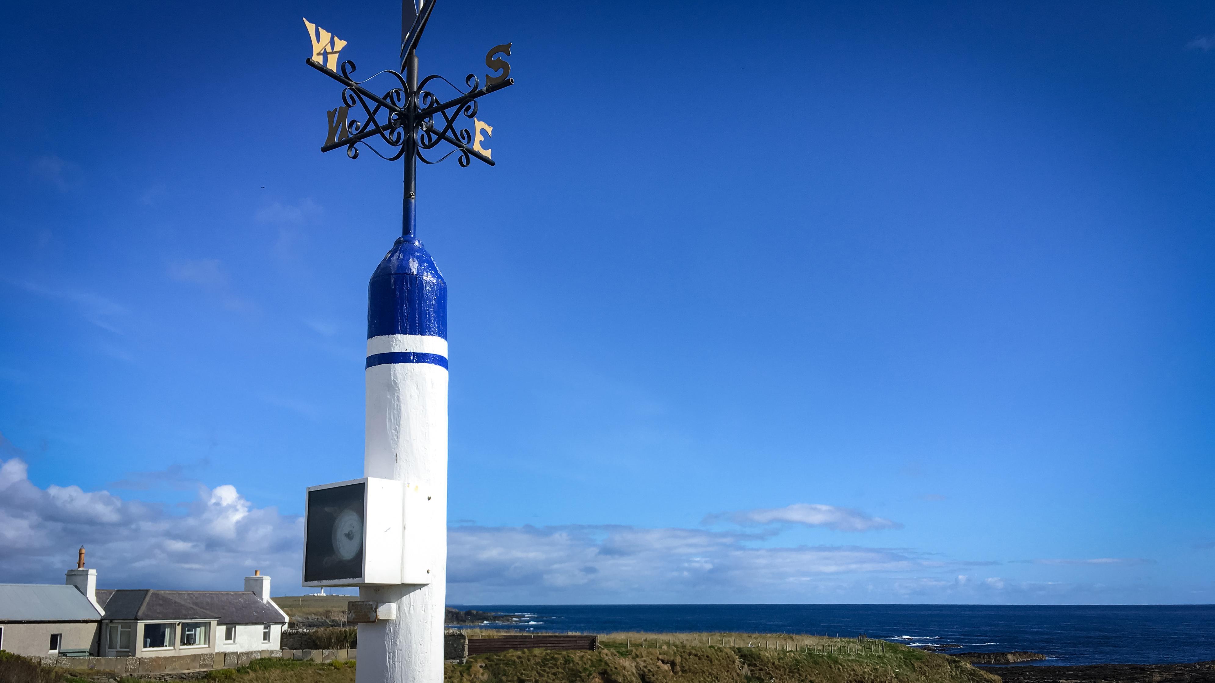 Messerät für die Windrichtung in Blau und Weiß am Meer