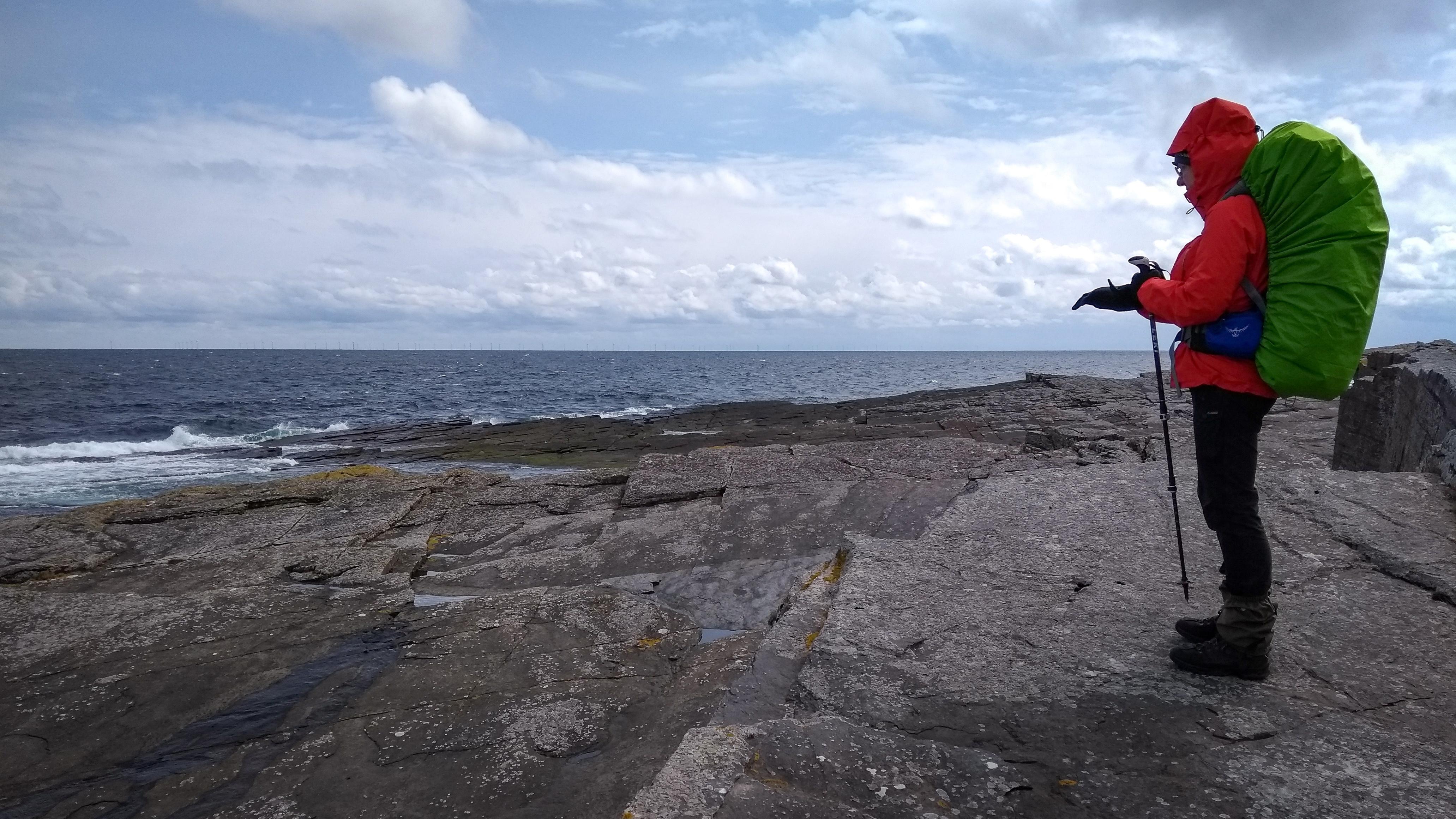 Frau steht mit Rucksack auf einer Felsenplatte am Meer, es ist Windig