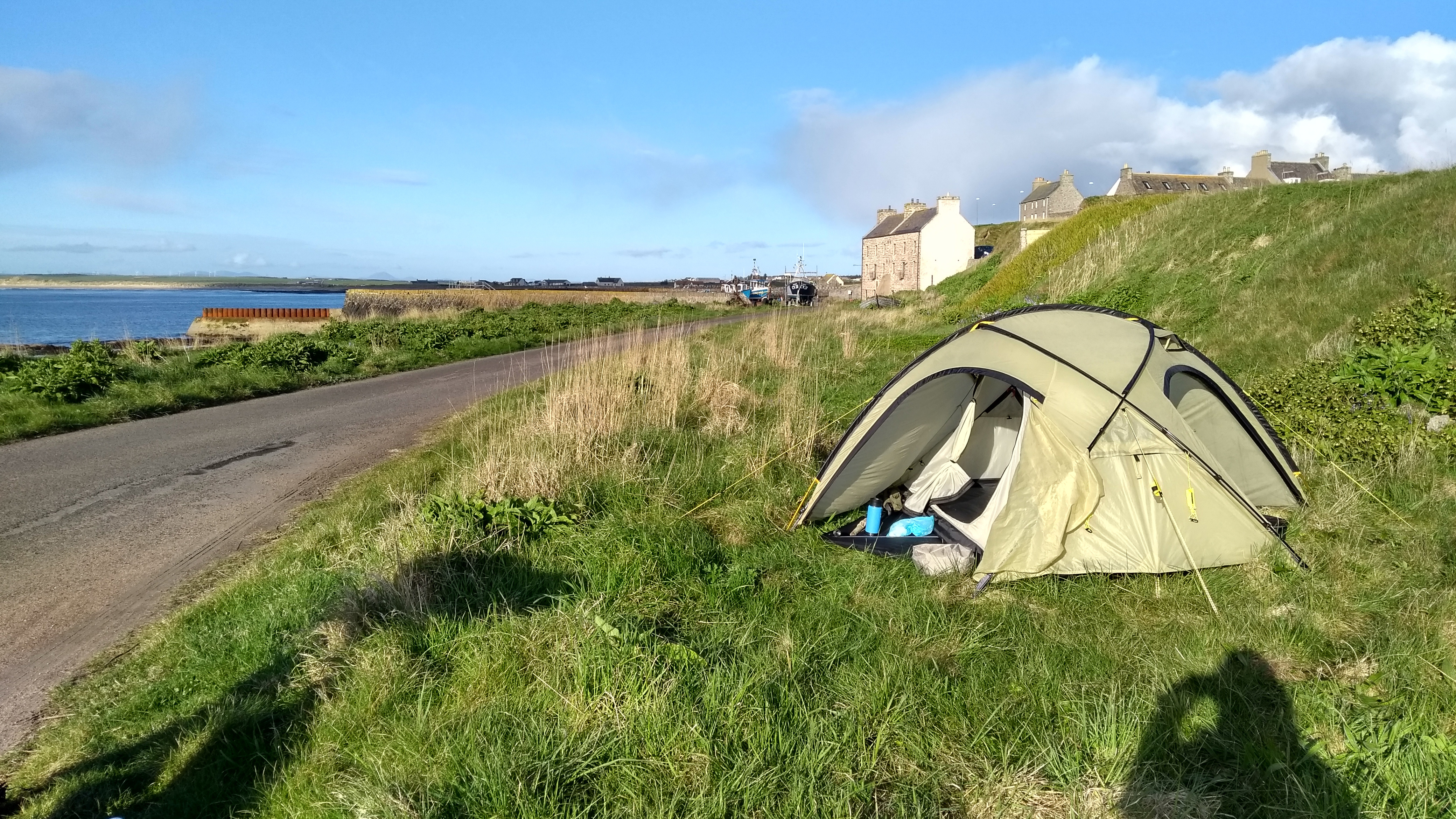 Zelt in der Kurve auf einem Grasstück am Hafen von Keiss