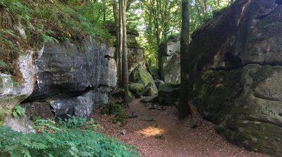 Waldweg zwischen Felsen und Lichtpunkt auf dem Weg