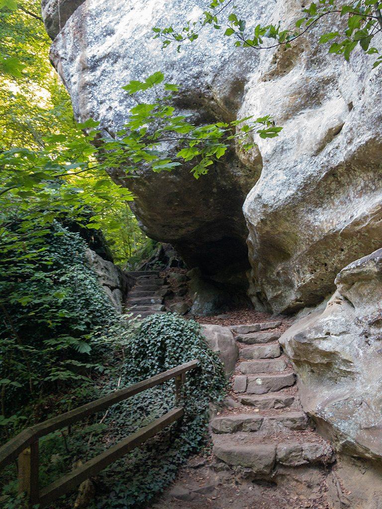 Überhängender Fels über einer Steintreppe im Wald