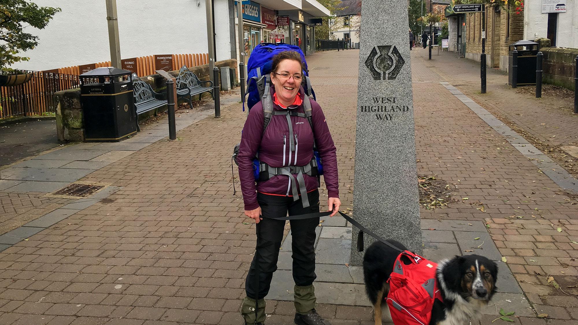 Frau mit Rucksack und Hund vor dem West Highland Way Stein in Milngavie