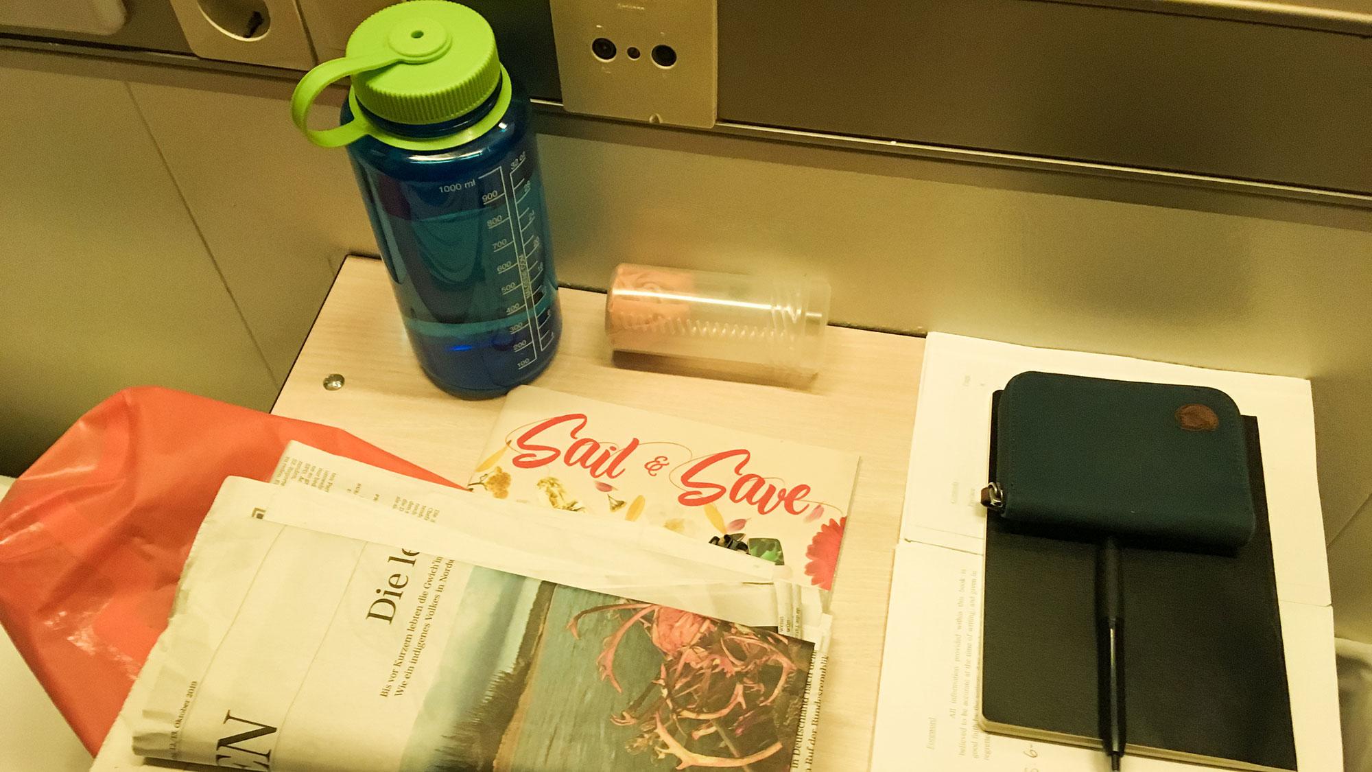Zeitung, Wasserflasche, Brillenetui, Tagebuch und Portmonaie auf Tisch in der Kabine der Fähre