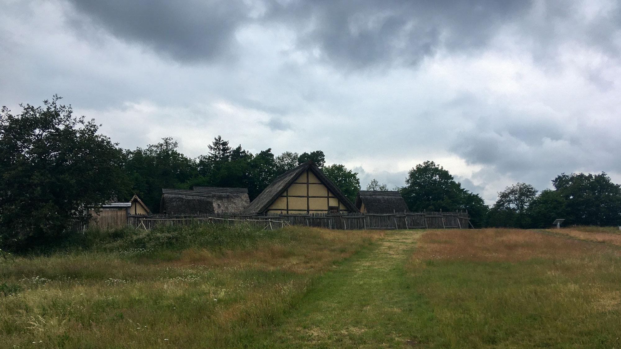 Umzäunte Keltensiedlung mit strohbedeckten Hütten