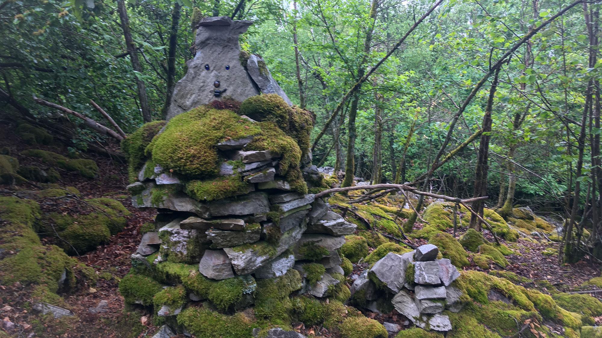 Bemoostes Steinmännchen mit Gesicht im Wald
