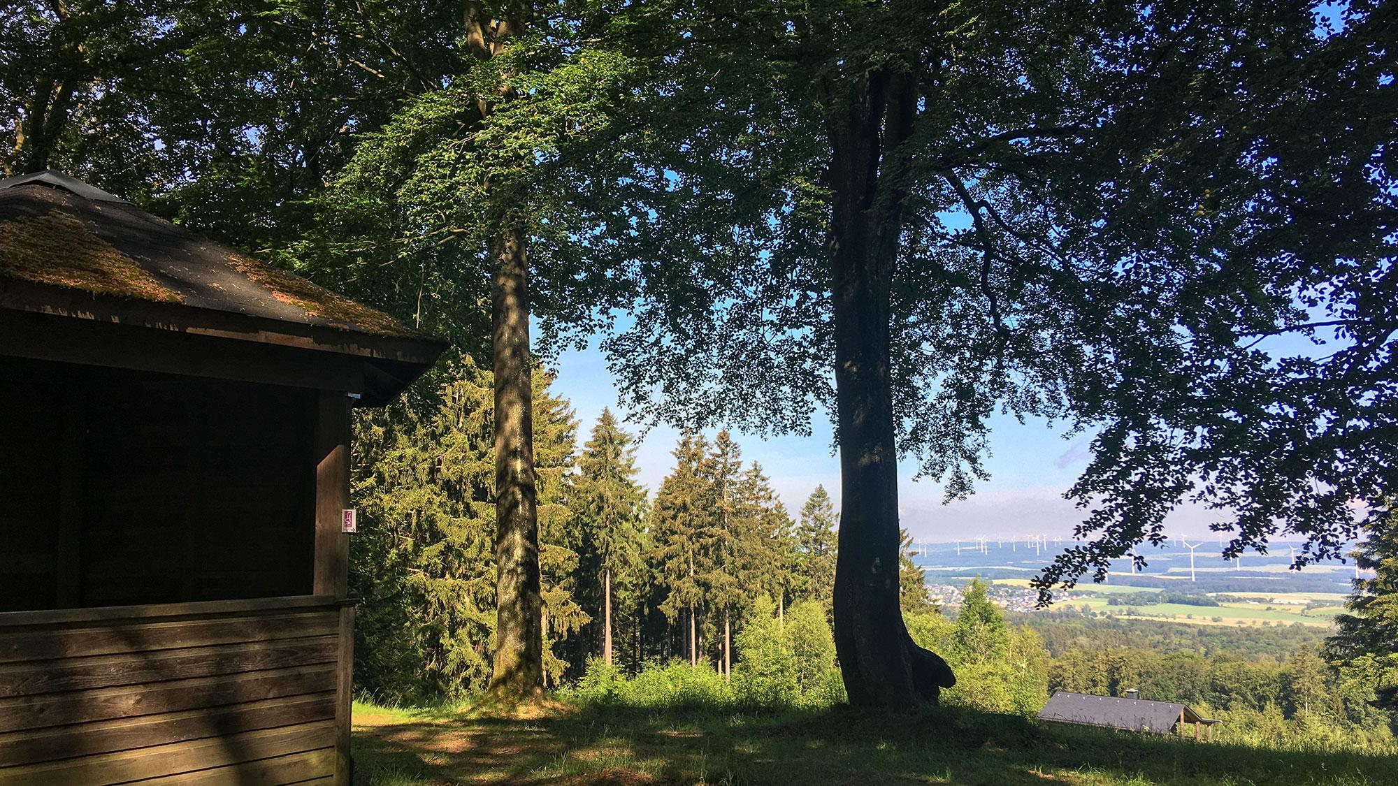 Holzhütte, dahinter Panorama im Sonnenschein