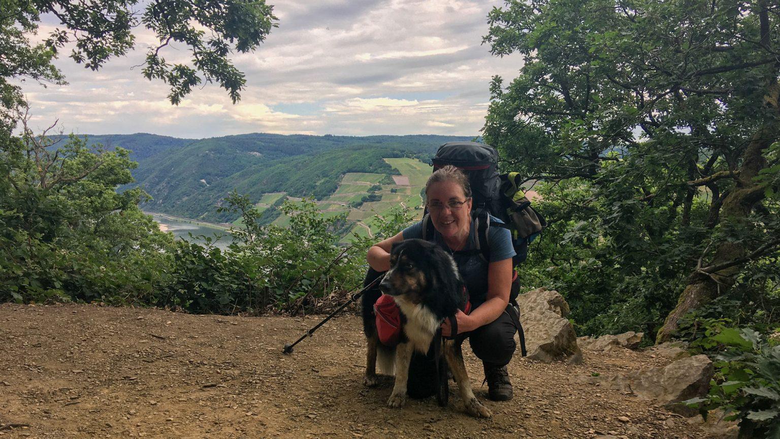 Wanderin mit Hund, dahinter der Rhein