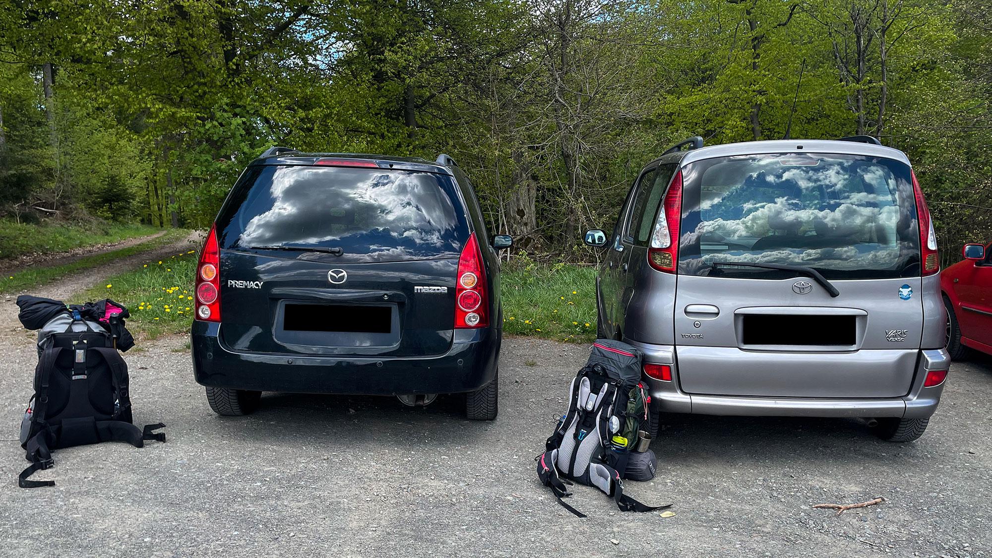Zwei PKW und zwei Rucksäcke am Wanderparkplatz
