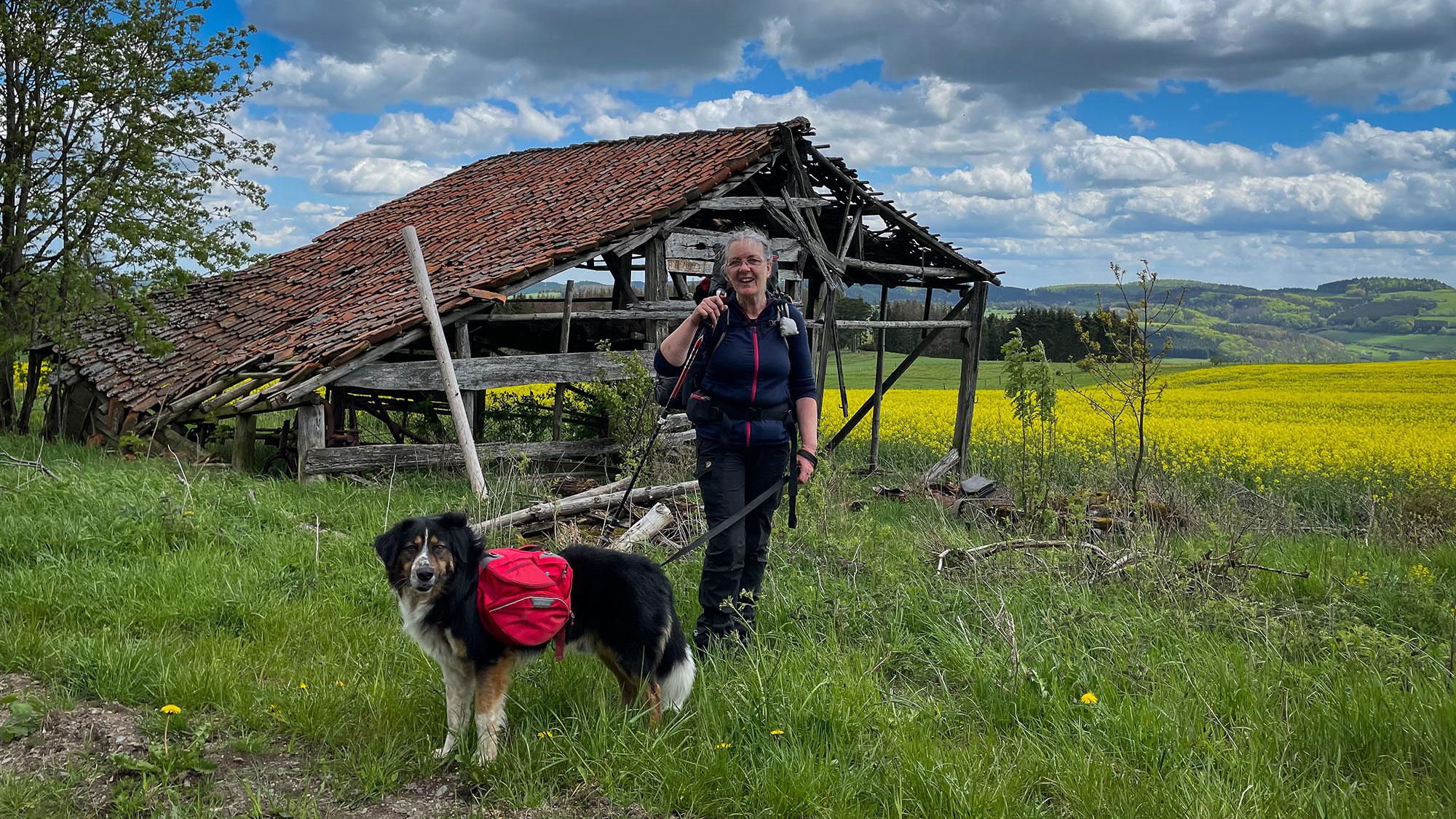 Frau und Hund mit Rucksack vor Scheune auf dem Uplandsteig